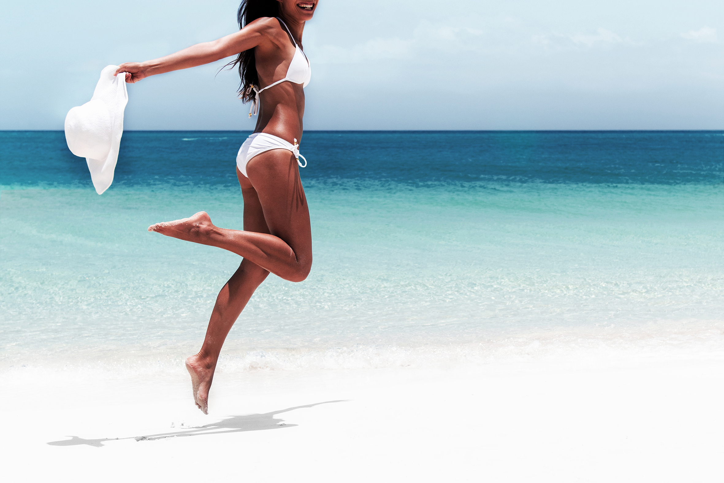 Beach Ready Bikini Body Sexy Slim Legs And Toned Thighs And Butt. Suntan Happy Woman Jumping In Freedom On White Sand With Sun Hat. Weight Loss Success Or Epilation Concept.
